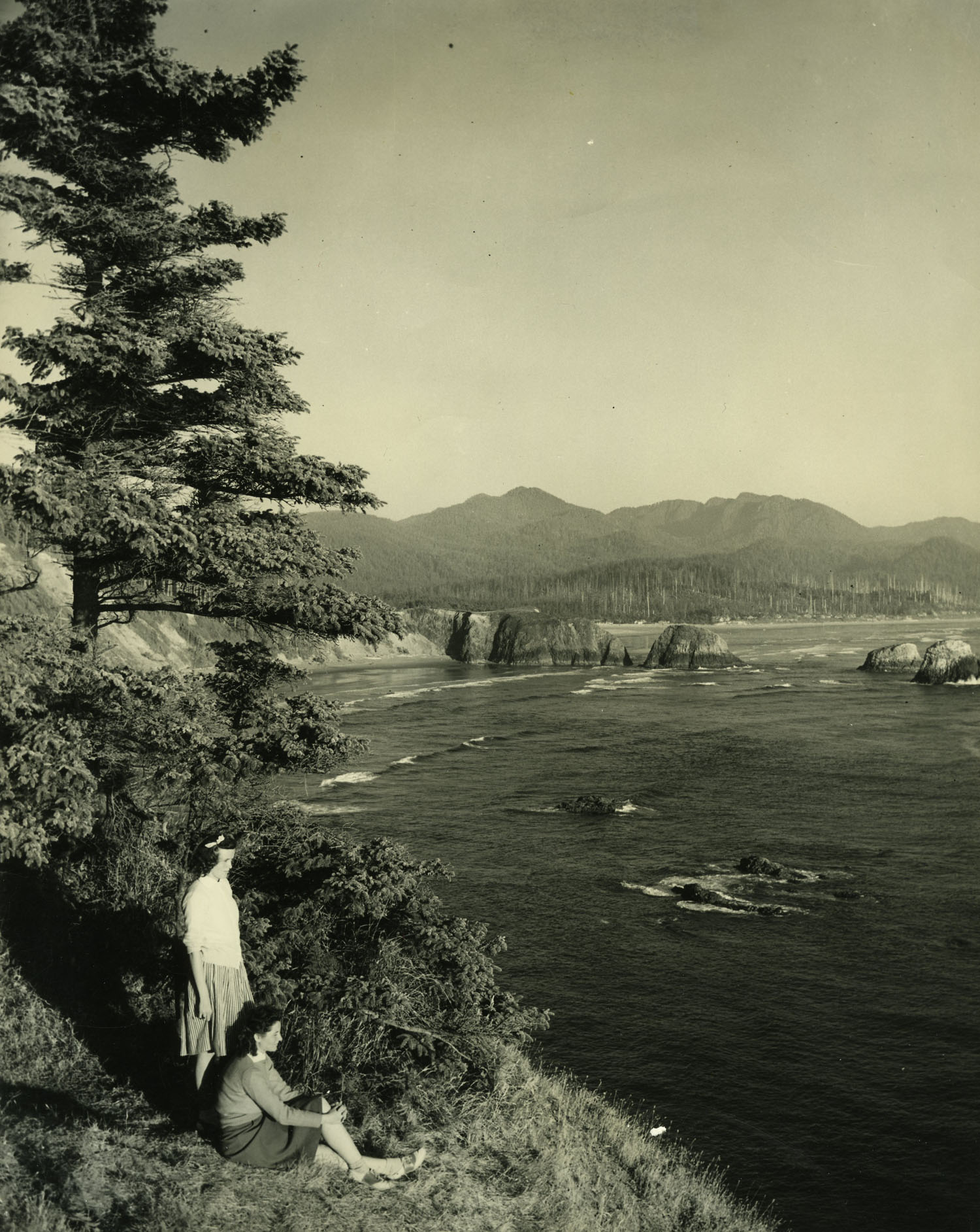 Two young women enjoy the view from the Ecola State Park trail, circa 1960.