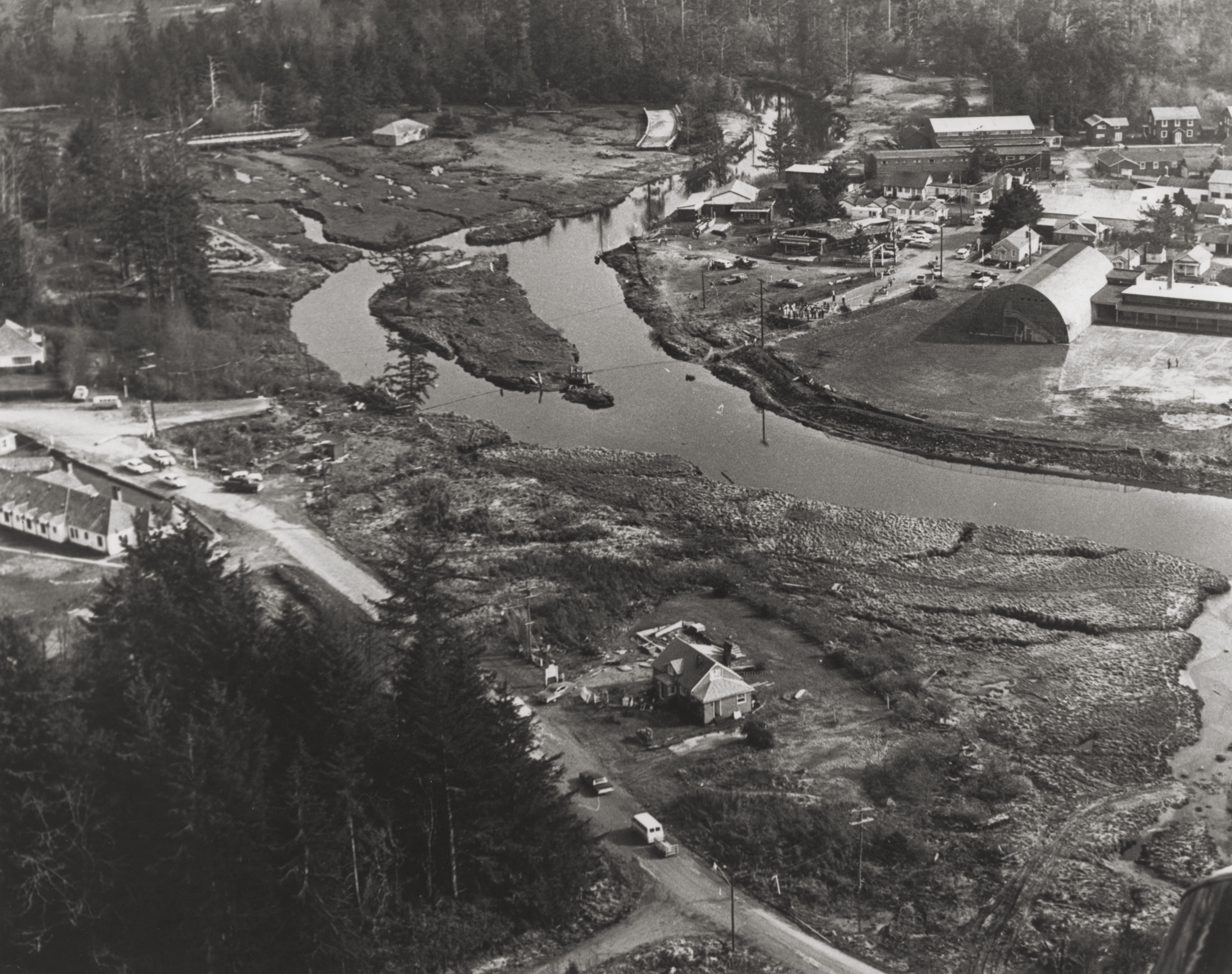 Tsunami damage from the 1964 Good Friday Quake. Note the pieces of bridge and the small white house in the background.
