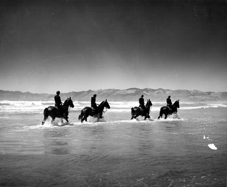 Members of the Coast Guard's mounted beach patrol cross an inlet during their patrol on the west Coast.  The use of horses allowed the Coast Guard personnel to cover wide stretches of beach more quickly than on foot. Image courtesy of the U.S. Coast Guard.